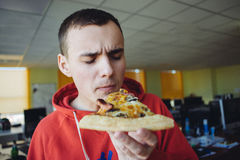 Portrait of a young man holding a large slice of pizza on a background of office. royalty free stock photography