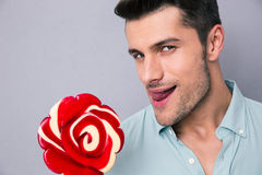 Portrait of a young man holding lollipop stock photography