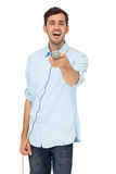 Portrait of a young man holding out microphone Royalty Free Stock Photos