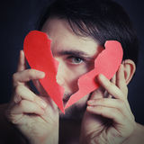 Portrait of a young man holding a paper broken heart Stock Photography