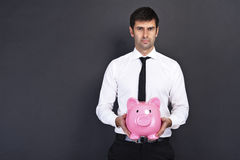 Portrait of young man holding a piggy bank Royalty Free Stock Photo