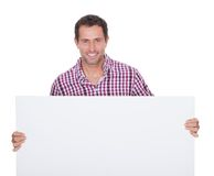 Portrait Of Young Man Holding Placard Stock Photo