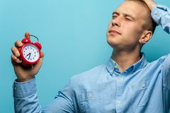 Portrait of young man holding red vintage clock stock image