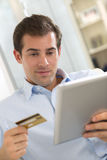 Portrait of young man holding tablet pc and credit card.indoor Royalty Free Stock Images