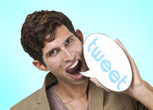 Portrait of young man holding tweet word bubble against white background Stock Photography
