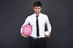 Portrait of young man holding a two piggy bank Royalty Free Stock Photography