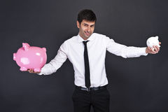 Portrait of young man holding a two piggy bank Royalty Free Stock Image