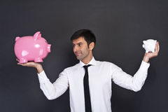 Portrait of young man holding a two piggy bank Royalty Free Stock Images