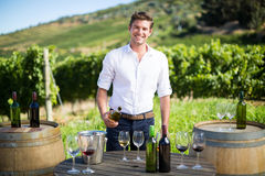 Portrait of young man holding wine bottle by table at vineyard Stock Photography