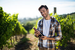 Portrait of young man holding wine bottle at vineyard Stock Image