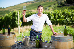Portrait of young man holding wineglass by table at vineyard Royalty Free Stock Image