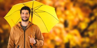 Composite image of portrait of young man holding yellow umbrella Royalty Free Stock Photography