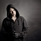 Portrait of the young man in a hood. Against a dark background Royalty Free Stock Photography