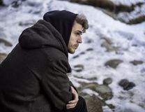 Handsome man in snow posing for camera. Portrait of young man in hoodie posing outdoor in winter setting with snow all around, looking away to a side Royalty Free Stock Photography