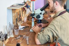 Appraiser Inspecting Stones. Portrait of young man inspecting precious stones using microscope sitting at workshop table royalty free stock photo