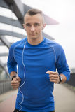 A portrait of a young man jogging on the bridge Stock Image