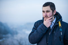 Portrait of a young man keeping hand on chin. Portrait of a young concentrated man keeping hand on chin making decision Royalty Free Stock Photography