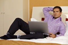 Portrait of young man with laptop on bed Royalty Free Stock Image