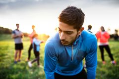 A portrait of young man with large group of people doing exercise in nature. royalty free stock photos
