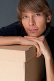 Portrait of young man leaning on box. Against grey wall. He is starting new life stock photo