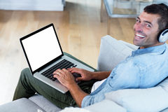 Portrait of young man listening to music while using laptop Stock Photo