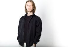 Portrait of young man with long blond hair, black shirt, white b Stock Image