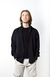 Portrait of young man with long blond hair, black shirt, white b Stock Images
