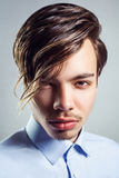 Portrait of young man with long fringe hairstyle on his eyes. Stock Images