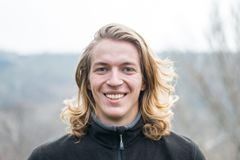 Portrait of a young man with long hair and a genuine smile, outdoors. Portrait of a man Stock Image
