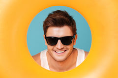 Portrait of young man looking out of the circle isolated. Portrait of young handsome man in sunglasses and white t-shirt looking out of the yellow swimming stock photos