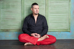 Portrait of a young man, lotus posture. Portrait of a young man, black shirt and red slacks, hairstyle with shaved temples and slicked- back hair at the top of Stock Images