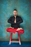 Portrait of a young man, lotus posture, red chair Royalty Free Stock Images
