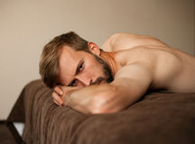 Portrait of young man lying on bed topless. stock images