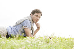 Portrait of young man lying on grass against clear sky Royalty Free Stock Photo