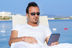 Portrait of young man lying on a sunbed reading with tablet Stock Images