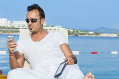 Portrait of young man messaging  on a sea background Royalty Free Stock Photo