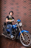 Portrait of Young Man on Motorcycle by Brick Wall Stock Photo
