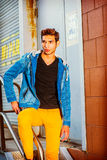 Portrait of Young Man in New York. Portrait of Young Worker. Wearing a blue jacket with hood, black underwear, yellow pants, a young handsome guy is standing by Royalty Free Stock Image