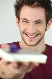 Portrait of a young man offering gift Royalty Free Stock Photography