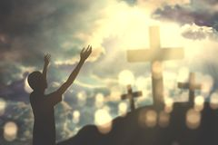Young man praising to God with crucifixes. Portrait of a young man opening arms while praising and praying to God with three crucifixes at the sunrise Royalty Free Stock Photos