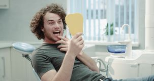 Portrait of a young man patient after visiting his dentist , sitting on blue dentist chair and happy looking through the. A yellow mirror and examined his stock footage