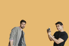 Portrait of young man photographing friend over colored background Stock Photo