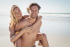 Portrait of young man piggybacking beautiful woman at beach Royalty Free Stock Images