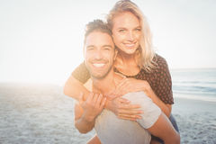 Portrait of a young man piggybacking beautiful woman Stock Image