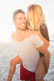 Portrait of a young man piggybacking beautiful woman Royalty Free Stock Images