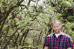 Portrait of young man. Portrait of young man in plaid shirt with greenery in the foreground Royalty Free Stock Images