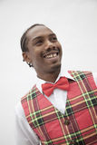 Portrait of young man in plaid vest and red bow tie, studio shot Royalty Free Stock Photos