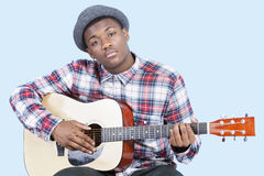 Portrait of a young man playing guitar over light blue background Stock Photos