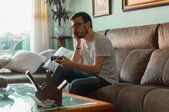 Young man playing video game holding wireless controller royalty free stock photos