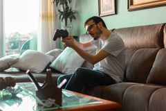 Young man playing video game holding wireless controller stock photos